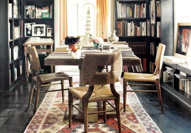 Home office with built in dark wood bookcases and matching dark wood floors, a reclaimed wood table surrounded by rope chairs on a patterned area rug