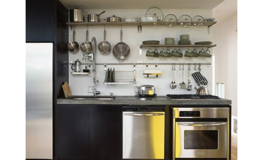 Kitchen with black cabinets with no visible drawer pulls, stainless appliances, a dark marble countertop and wall mounted pot rack