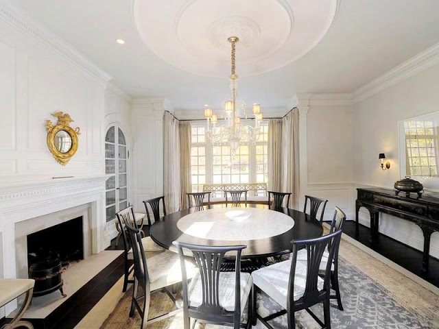 Formal dining room features a fireplace, a grand ceiling medallion and a round dark wood dining table that seats 10