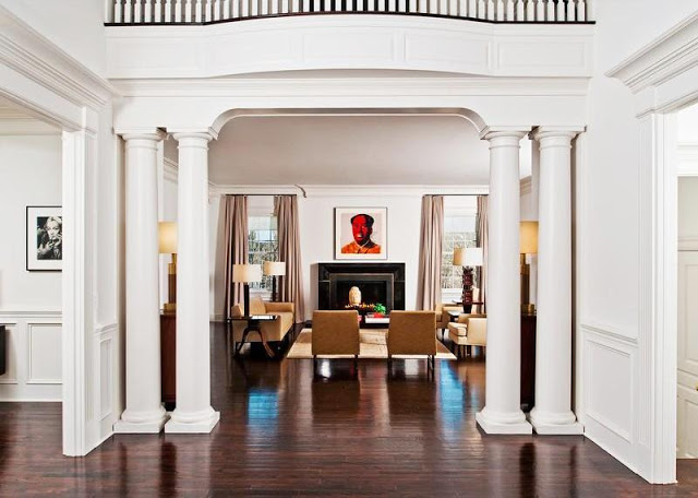 foyer in a mansion with white columns and a wood floor with a view into the living room