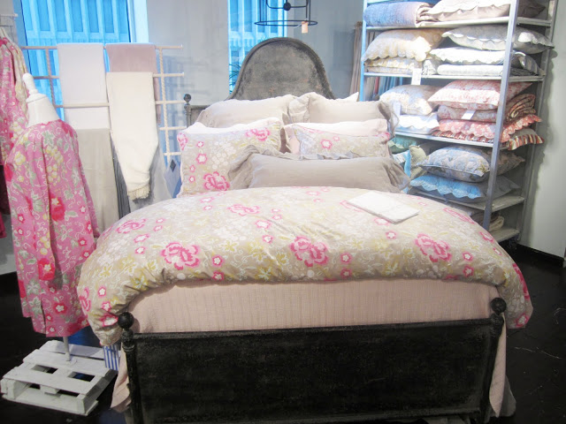 Pine Cone Hill's section of the with chintz and mesh bedding on a metal bedframe with curved headboard at the Christian Mosso Associates showroom