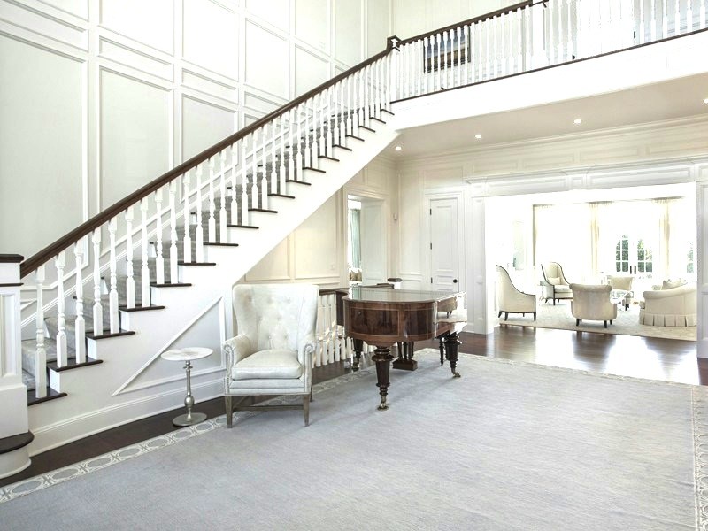 Entry Hall Sets The Traditional Decor Tone Of Home And Features A Stairs Leading To Second Floor Balcony Paneled Wall Above