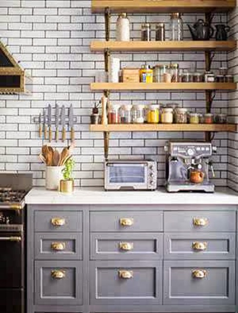 Kitchen in a New York apartment with grey cabinets with brass pulls, wall mounted shelves, marble countertops and subway tile walls on dark grout