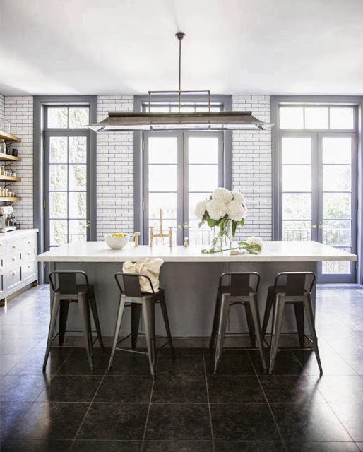 Kitchen in a West Village apartment with subway with dark grout walls, grey cabinets, French doors and large kitchen island