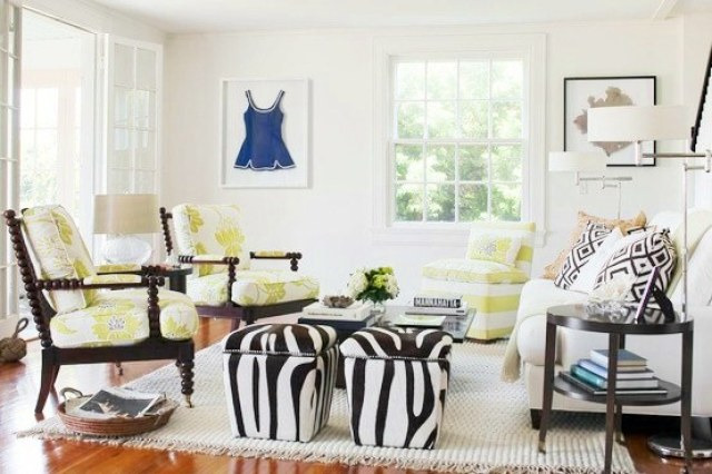 beach cottage with chic zebra print ottoman, graphic floral upholstery arm chairs and a white sofa with graphic accent pillows, a wood floor and a white rug