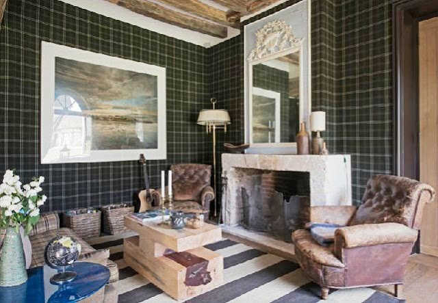 den with plaid walls and a striped rug with exposed beams, leather chairs, fireplace with a trumeau mirror on the mantel