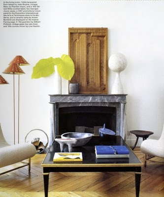 Living room with herringbone wood floor, a marble fireplace, and a black lacquer coffee table. On the table is a Yves Klein blue book