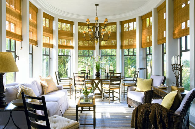 Informal dining room in a South Carolina estate with woven shades, rattan arm chairs, and a white sofa