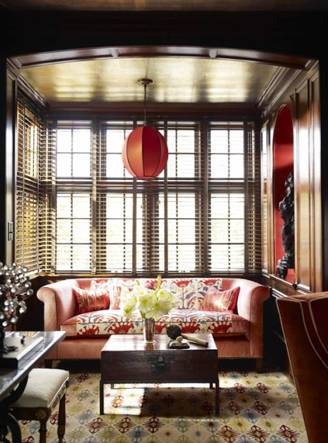 Study with coral sofa with patterned throw, chest converted into a coffee table, dark wood walls, a patterned area rug and a red pendant light