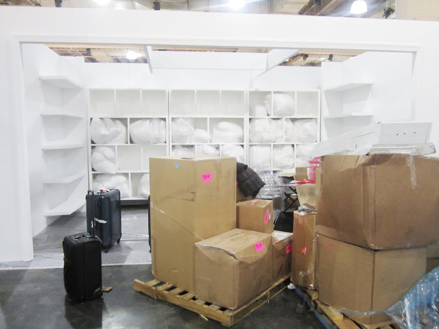 White lacquer display with floating shelves with boxes holding the rest of COCOCOZY's booth for the New York International Gift Fair