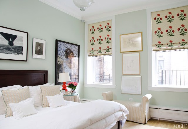apartment bedroom with mint walls, a wooden headboard, white bedding and floral roman shades.
