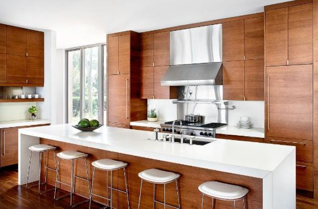 modern kitchen with wood cabinets, white caesar stone counters and white barstools