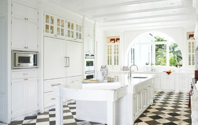 All white kitchen with checkered marble floor and an arched window