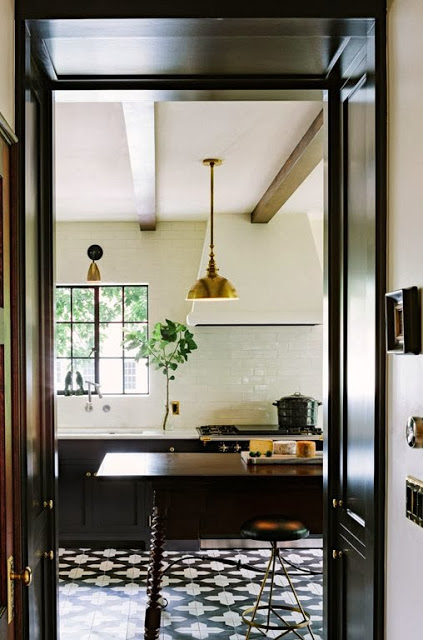 Modern kitchen with cement tiles, black cabinets, and brass pendant lights