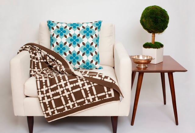 COCOCOZY throw draped across a white armchair with a COCOCOZY pillow next to a wooden side table holding a small topiary and metal bowel