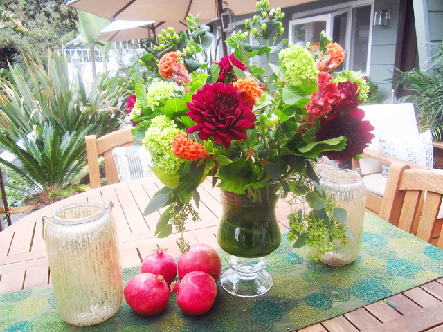 Flower arrangement with dahlia, cockscomb, green coffee beans, seeded eucalyptus, baby hydrangeas and tea leaves on a table in a backyard