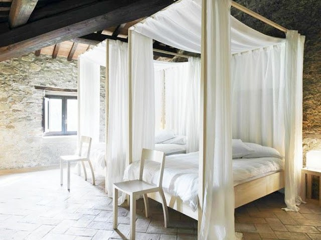 Two canopy beds in a bedroom with stone walls and floor with wispy white drapes and white linens