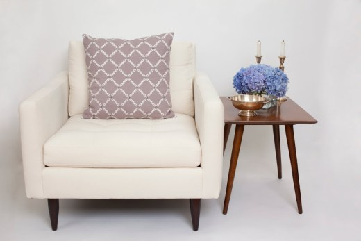 COCOCOZY Cotton Collection pillow in Kip on a white armchair next to a wood side table with two candlestick and a bouquet of hydrangeas
