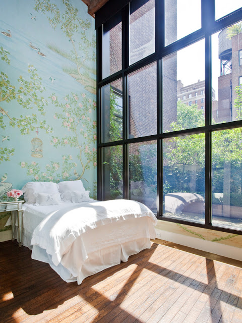 bedroom with iron framed floor to ceiling windows with a view, a large wall with floral wallpaper, a wood floor and a simple white bed