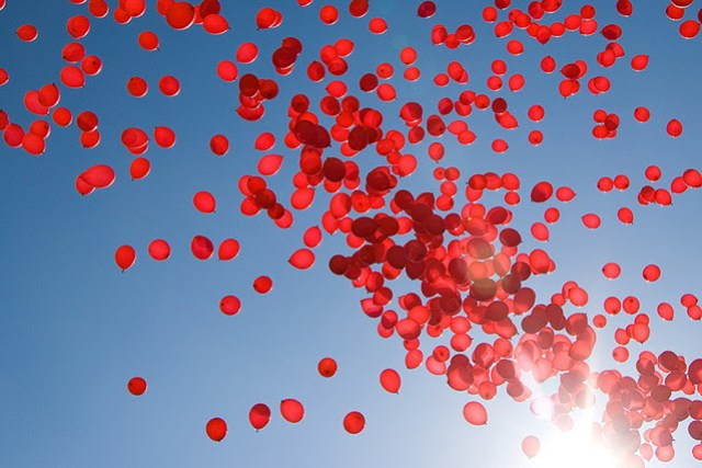 a bunch of red balloons being released into a blue sky