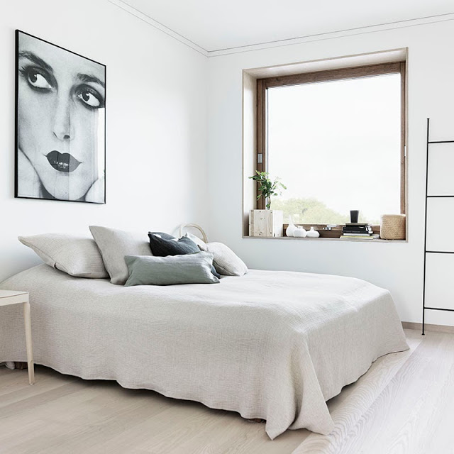 Clean white bedroom with light wood floor, a large window and a framed portrait