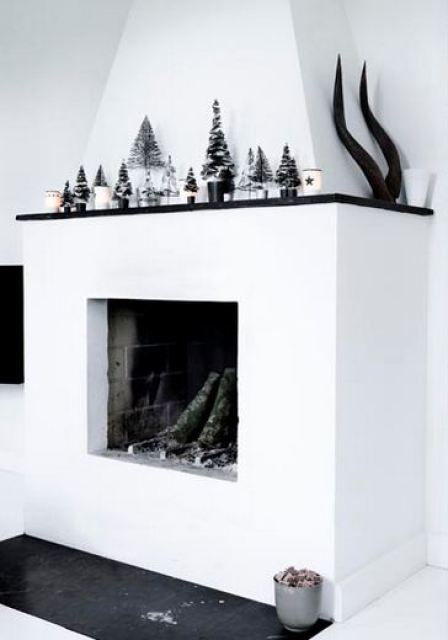 black, white and silver line klein holiday display with a fireplace, on the mantel there are silver miniature christmas trees and candles