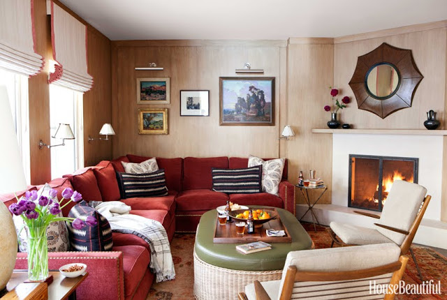 cozy family room with red sofas and a fireplace by Peter Dunham