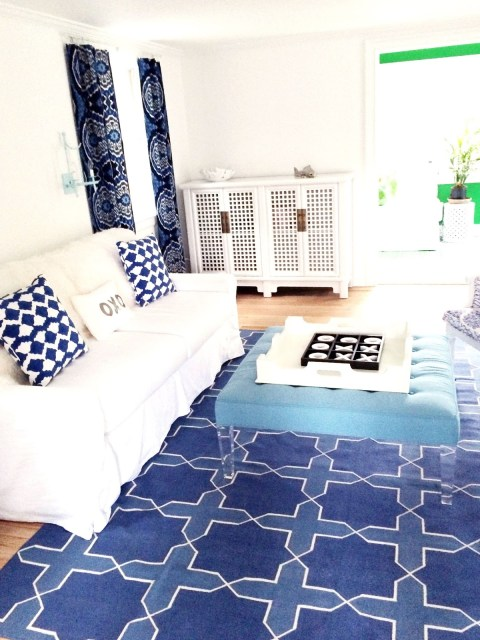 Blue and white living room with an ottoman with lucite legs in an East Hampton home