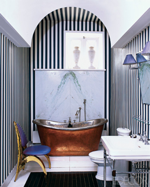 "Bathroom with black and white vertical striped wallpaper, a brass stand alone tub wit ha marble backsplash, a black tile ""rug"" and a chair with metal legs and back painted yellow and blue cushions"