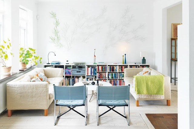 Living room with dueling white sofas, two chairs with blue cushions, a wood floor and a wall length bookcase stuffed full of books