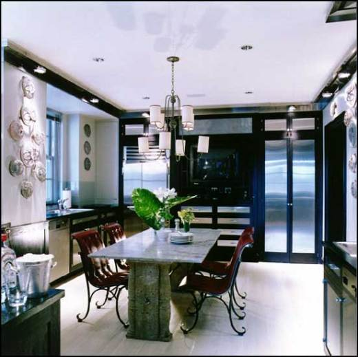 Eat in kitchen with black cabinets with stainless doors, white walls and tiled floor, a stone table with marble tabletop is surrounded by red leather upholstered chairs with wire legs.