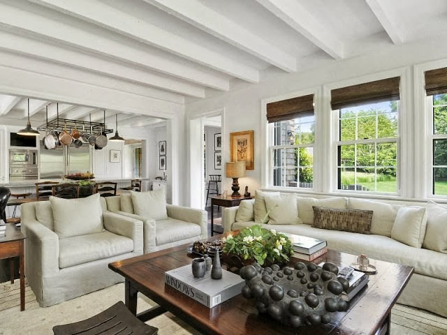 Open plan living room of a house on an East Hampton compound with grey sofas and armchair and beamed ceiling