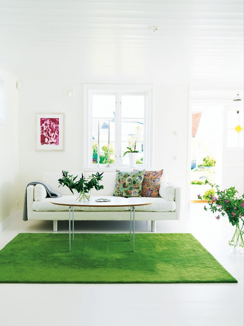 White living room with an oval coffee table and sofa with a grass green rug