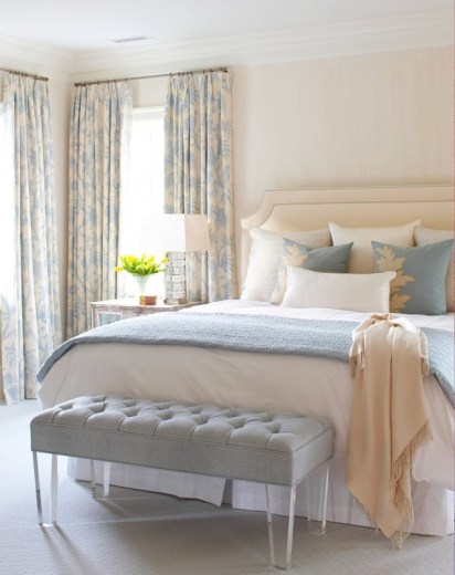 Bedroom in a cottage with blue and cream floor length curtains, a blue tufted ottoman at the foot of the bed, a cream upholstered headboard with blue, white and cream accent pillows