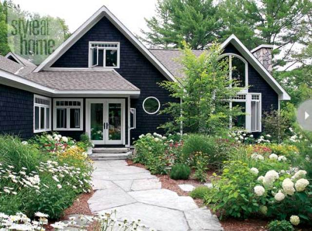 charcoal gray cottage house with white trim flagstone path garden