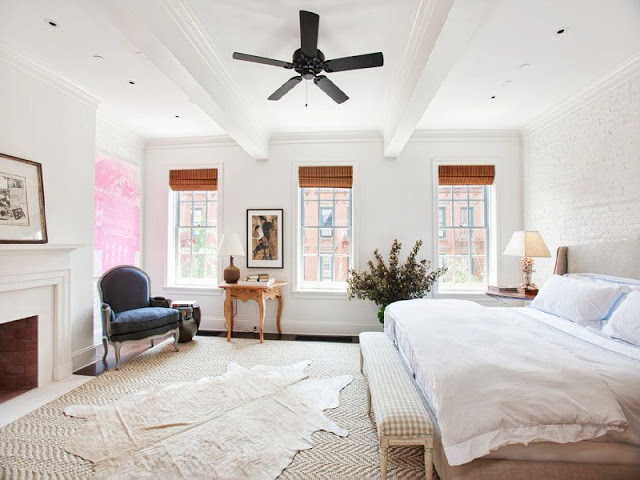 Master bedroom with a lot of natural light, fireplace, a large bed with a nightstand and a blue armchair in the corner.