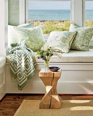 Close up of the COCOCOZY throw in a window seat vignette with an ocean view in the Coastal Living Magazine