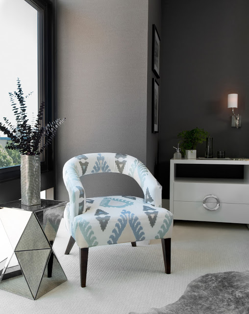 Close up of an upholstered chair with a mirrored side table in a grey bedroom