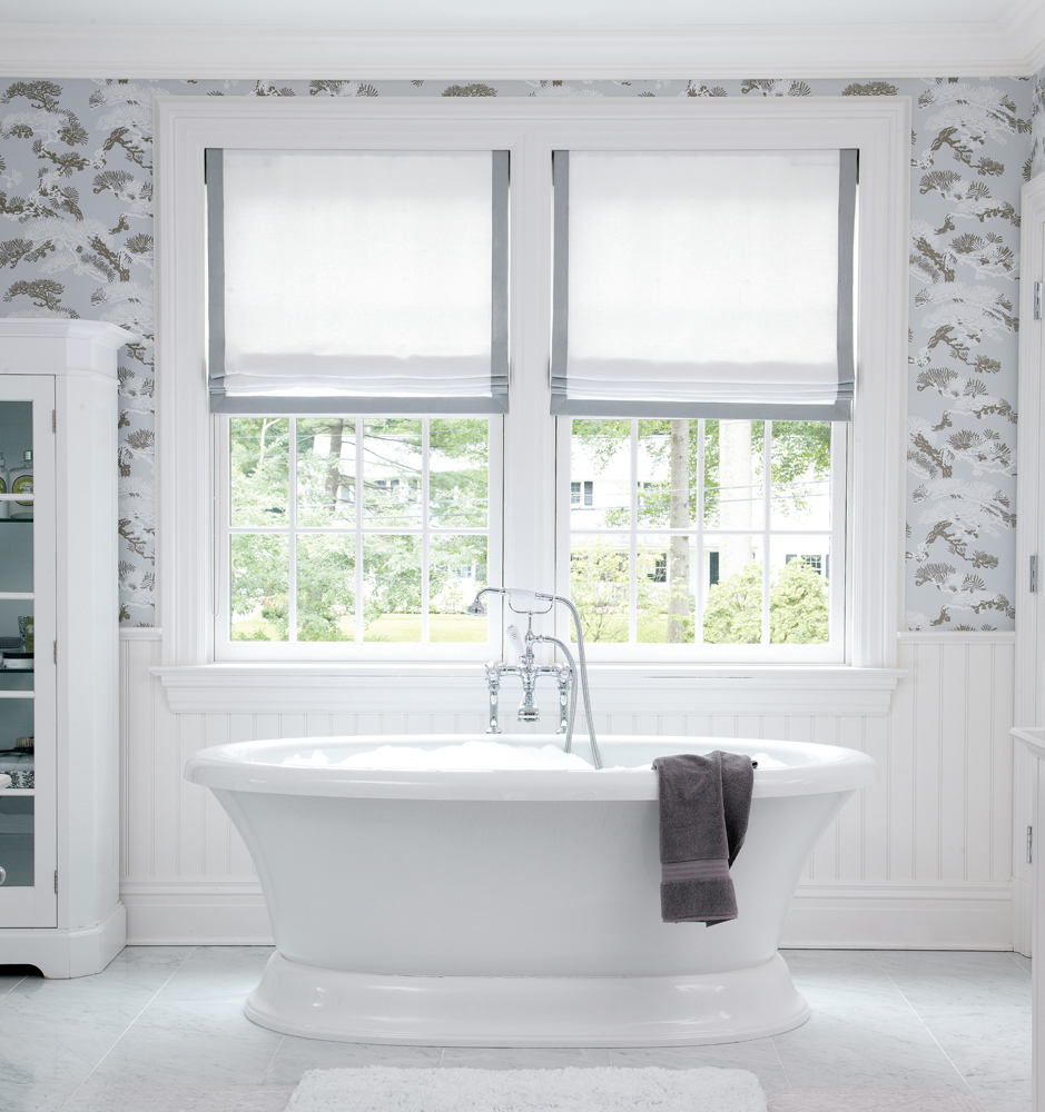 a well appointed traditional bath with tub light blue and gray floral wallpaper and roman shades trimed in gray above