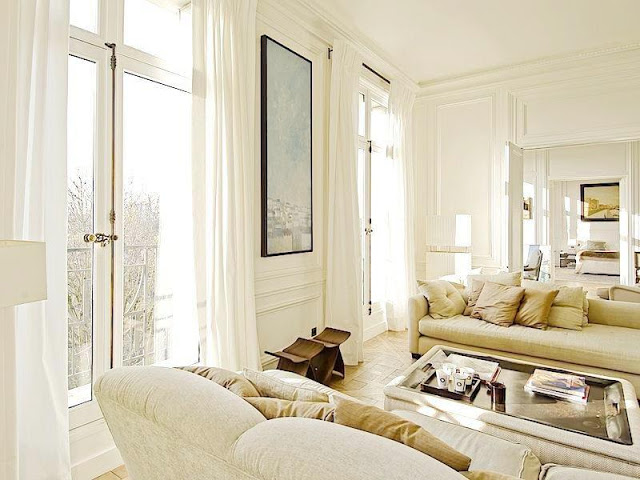 living room with high ceilings, floor length white curtains, neutral dueling sofas, molded walls and a glass coffeetable