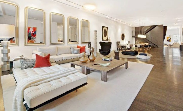 alternative view living room in a Soho Condo in New York with white sofa, gray table, decorative mirrors and orange accents