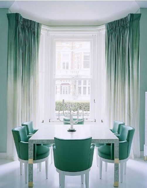 Ombre sea foam green curtains and chairs in the dining room with a large window and white candlestick holder