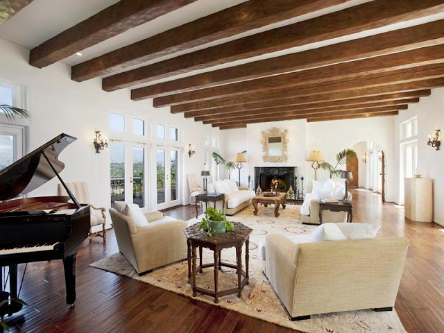 Living room with fireplace, arched doorways, wood floors, exposed wood beam ceiling, grand piano, dueling sofas with matching arm chairs and Moroccan side tables