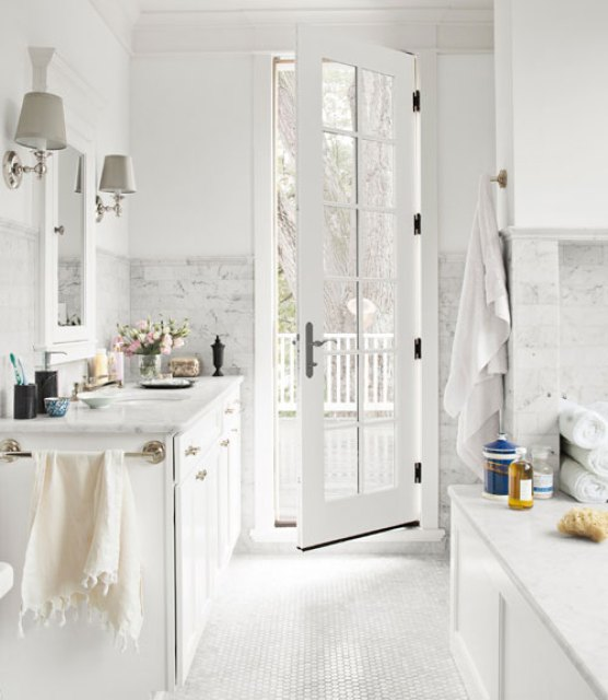 White bathroom with Carrara marble floors=in the form of a hexagon mosaic, counters and tub surround, a French door leads to a patio