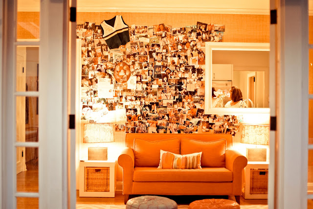 Orange den with  orange sofa, large mirror, small accent tables and photo wall that overlooks the backyard