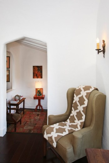Entryway in a 1920's Spanish style home with a wingback chair and a COCOCOZY Gate throw