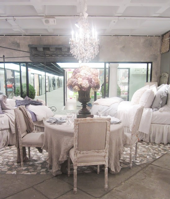 Christian Mosso Associates showroom with a round table surrounded by painted chairs, a crystal chandelier and a large goblet style vase holding a bouquet of hydrangeas