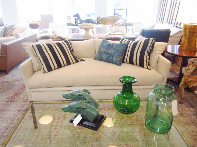 white couch with striped pillows on a vintage rug with a glass coffee table holding two green glass jars and a bust of two dogs