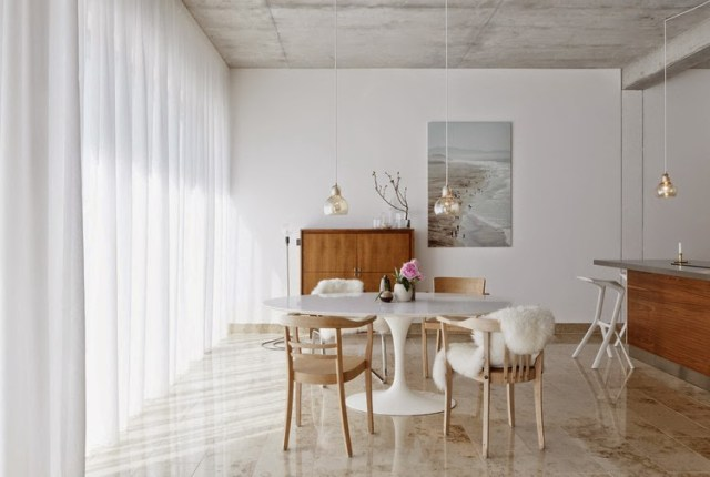 Bright grey and white dining room with mismatched chairs and a white Panton table