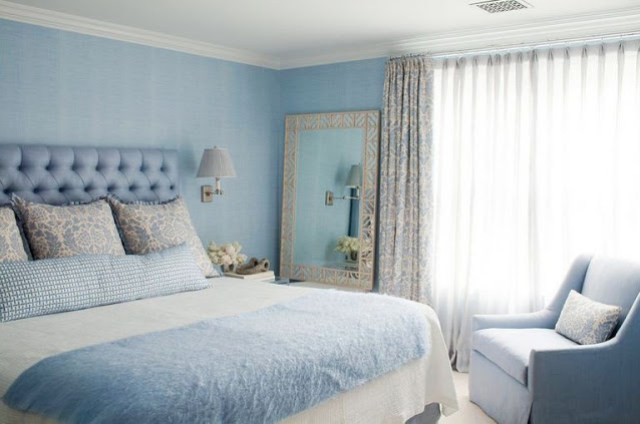Cornflower blue bedroom by Amanda Nisbet's with tufted headboard, arm chair, large mirror and floor length curtains